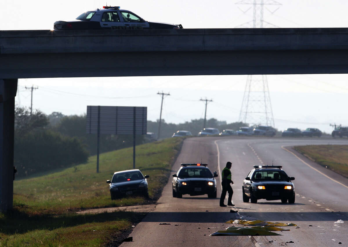 San Antonio police monitor the scene of a fatal incident at Loop 1604 westbound and Green Mountain where a man allegedly jumped off a freeway overpass about 7:00 a.m. and was hit by a passing 18-wheeler tractor trailer truck. The man was killed on impact and traffic in the area was backed up for at least a mile in the west lane of 1604. John Davenport/© 2010 San Antonio Express-News