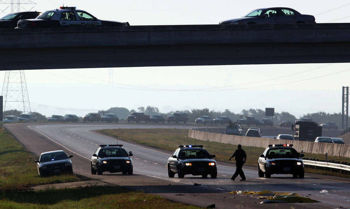 San Antonio police monitor the scene of a fatal incident at Loop 1604 westbound and Green Mountain where a man jumped off a freeway overpass about 7 a.m. and was hit by a passing 18-wheeler tractor trailer truck. The man was killed on impact and traffic in the area was backed up for at least a mile in the west lane of 1604.