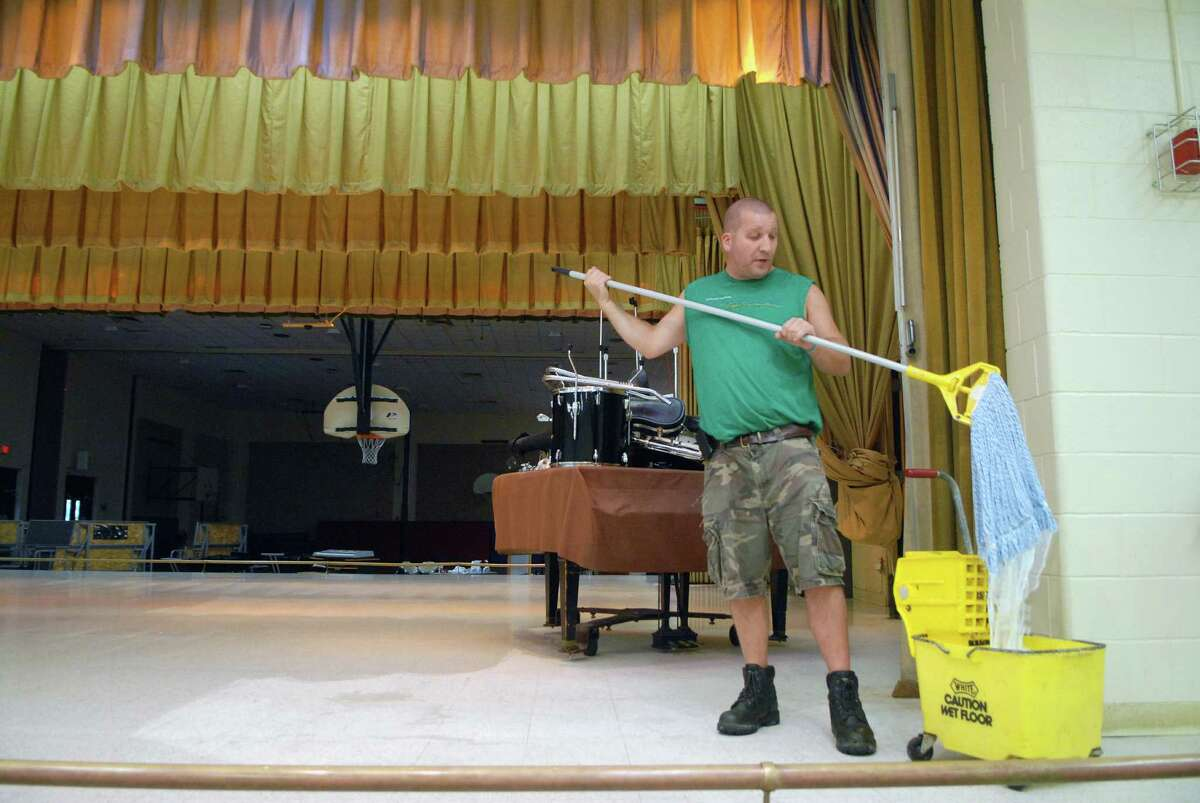 Head custodian John Calorossi waxes the stage on Monday August 20, 2012 getting Stillmeadow School in Stamford, Conn. ready for the return of students.