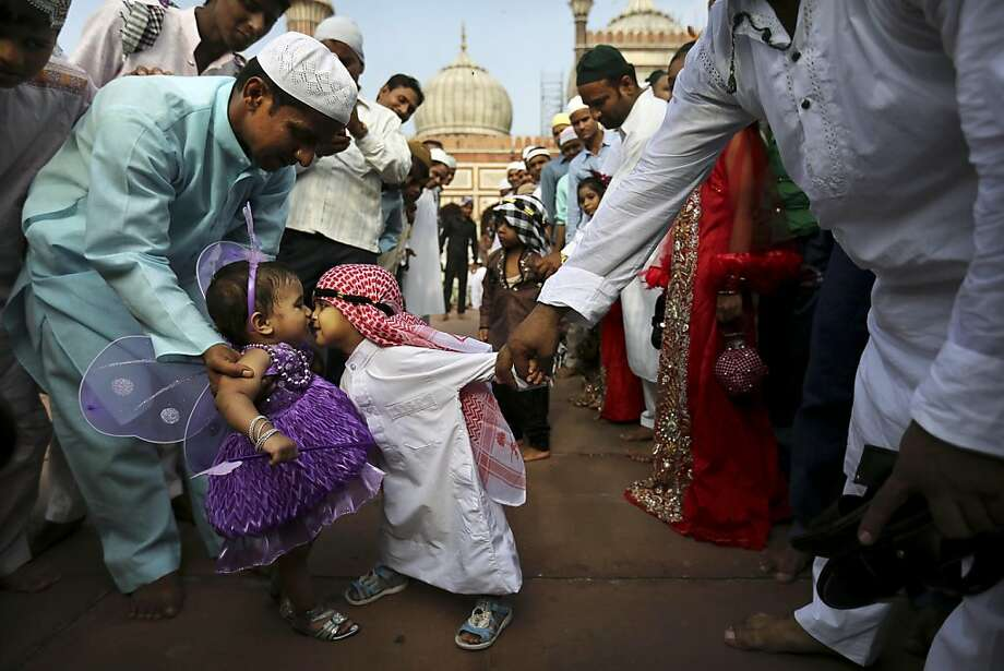 Overcome by the love bug:A young Indian Muslim boy leans in to rub noses with the opposite sex at Eid al-Fitr prayers in New Delhi. Photo: Kevin Frayer, Associated Press