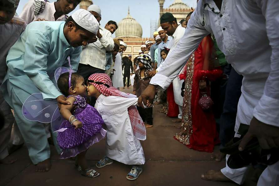 Overcome by the love bug: A young Indian Muslim boy leans in to rub noses with the opposite s