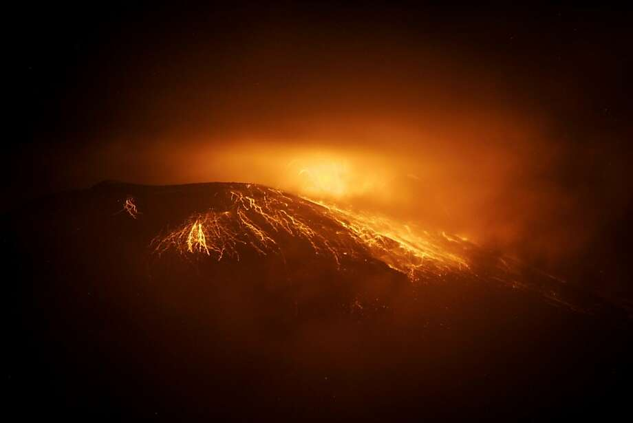 """Geological indigestion:Ecuador's Tungurahua Volcano glows orange  as it spews incandescent rocks and lava about 80 miles south of Quito.  Authorities issued an """"orange alert"""" (heightened volcanic activity) for  surrounding villages. Photo: Carlos Campana, AFP/Getty Images"""