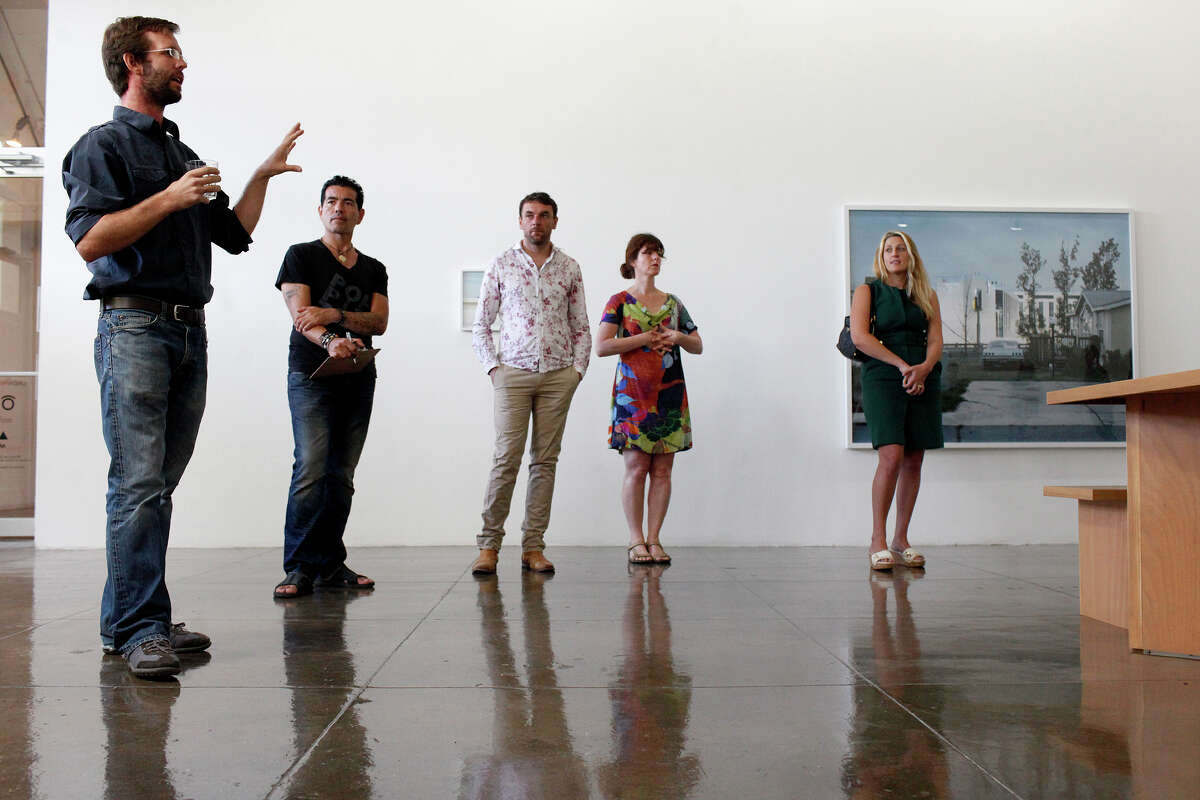 Photographer Mike Osborne (left) talks about his work during a preview at Artpace.