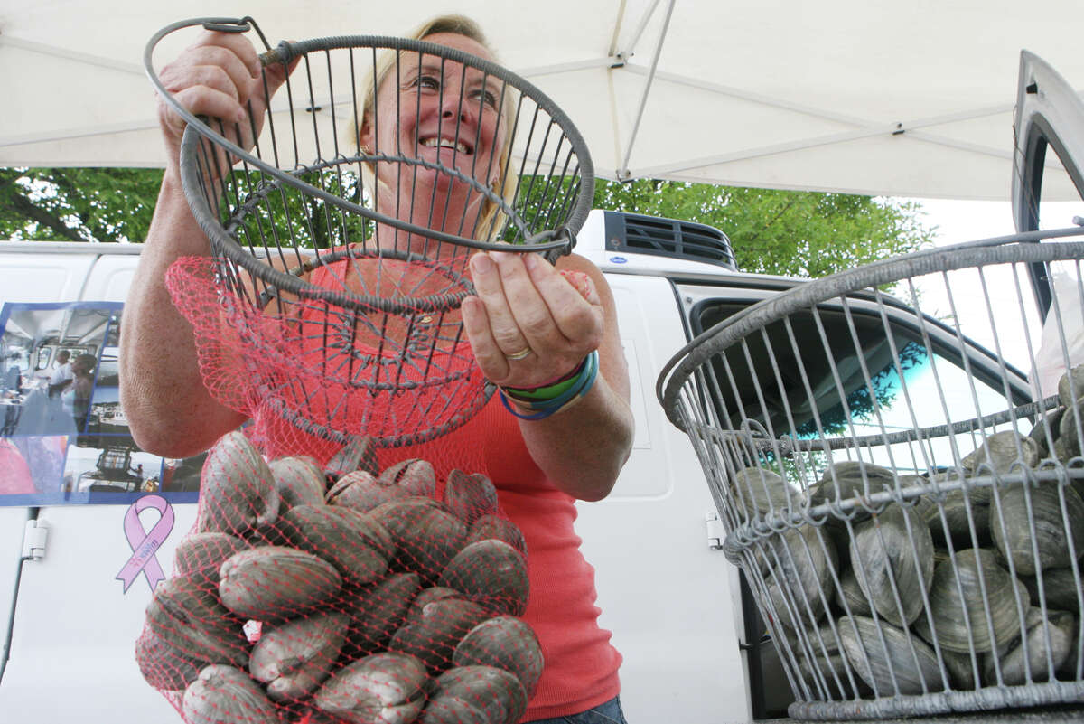 Laurie Popadic of Pepe's Cream of the Crop Shellfish bags clams for a customer at the Stratford Farmers market at Deluca Field on Monday, August 20, 2012. Laurie works with her husband Ed.