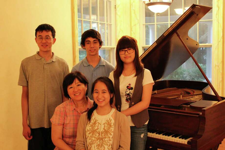 Among the students performing in a concert to raise money for an orphanage in Ecuador are, standing from left, Brian Wei, Michael Leone and Christine Chang. Seated, piano instructor Kyong Hee Cho and Angela Suh. Photo: Contributed
