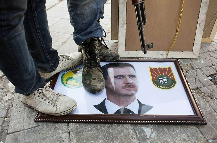 Syrian rebels stand on a picture of President Bashar Assad in the northern city of Aleppo. In the southwest city of Daraa, activists report raids, executions and intensified shelling. Photo: Achilleas Zavallis, AFP/Getty Images