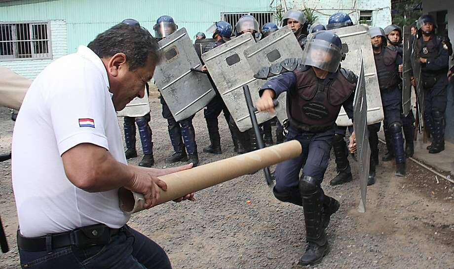 Taking cardboard to a nightstick fight:A Paraguayan Treasury Department civil servant wields a cardboard tube against the truncheons and shields of riot police during a protest demanding pay raises in Asuncion. Photo: Norberto Duarte, AFP/Getty Images