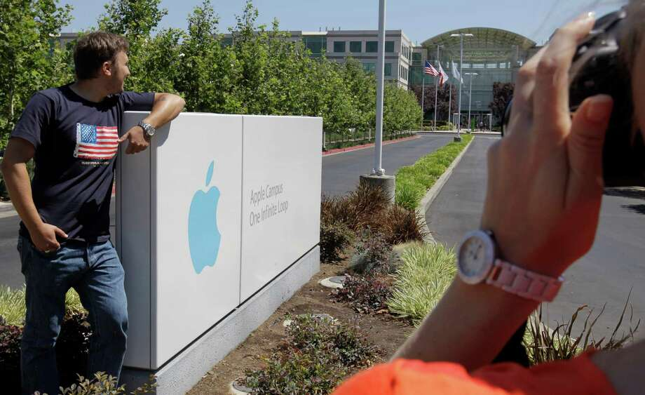 Russian tourists pose outside of Apple headquarters in Cupertino, Calif., on Monday, where the company's value eclipsed the mark set by Microsoft in 1999. Photo: Paul Sakuma / AP