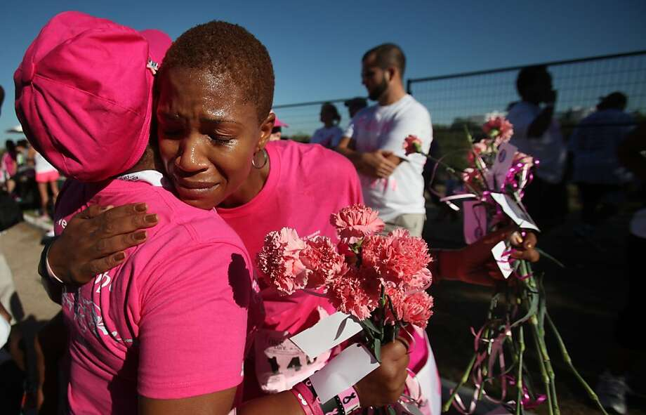 Two cancer survivors embrace each other at the end of the Susan G. Komen Race for the Cure last year in Houston. Photo: Mayra Beltran, Houston Chronicle