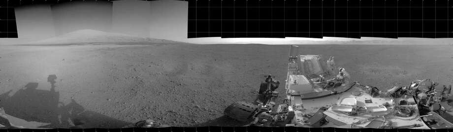 "This NASA image released August20, 2012 shows a panorama of the Mars Curiosity and Mount Sharp visible from the rover made from several images captured by several Navcams on board the rover. The Martian mountain rises 3.4 miles (5.5 kilometers) above the floor of Gale Crater. Geological deposits near the base of the Mount Sharp are the destination of the Curiosity rover's mission.  AFP PHOTO/HANDOUT/ NASA/JPL-Caltech      = RESTRICTED TO EDITORIAL USE - MANDATORY CREDIT "" AFP PHOTO / NASA/JPL-Caltech  "" - NO MARKETING NO ADVERTISING CAMPAIGNS - DISTRIBUTED AS A SERVICE TO CLIENTS =HO/AFP/GettyImages Photo: HO, AFP/Getty Images / AFP"