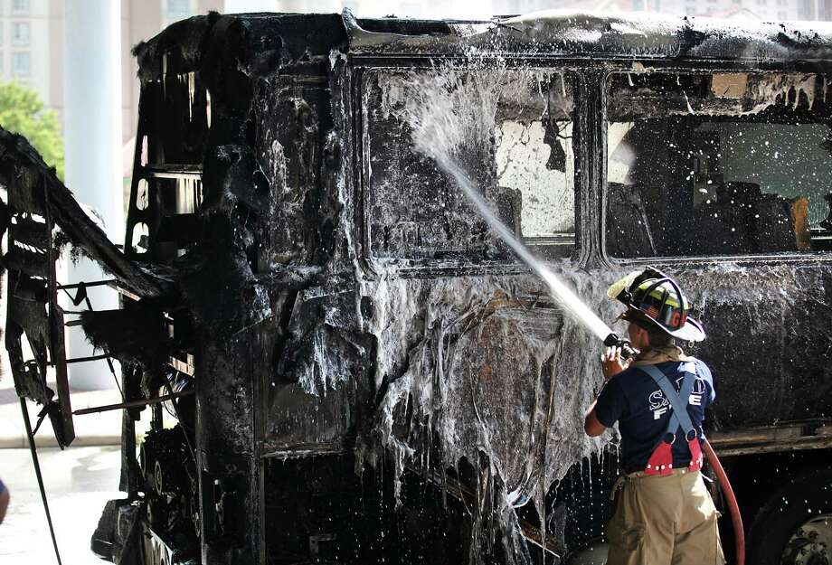 San Antonio fire fighters douse a fire on an Americanos Bus Line bus on E. Houston under I-37, Monday, August 20, 2012.  All passengers were able to exit the bus safely and there were no injuries. Photo: BOB OWEN, San Antonio Express-News / © 2012 San Antonio Express-News