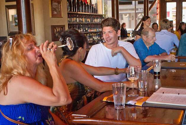 People enjoy wine and beer during happy hour at the Bounty Hunter in Napa. Photo: John Storey, Special To The Chronicle
