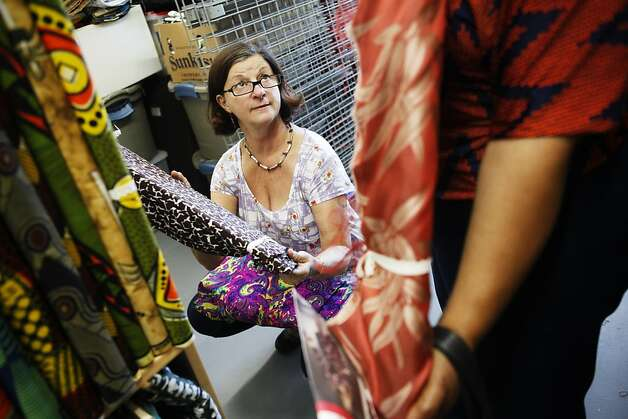 Electra Skilandat helps a customer find just the right fabric at her Urban Burp shop in Point Richmond, where she offers textiles going back to the 1920s. Photo: Sonja Och, The Chronicle