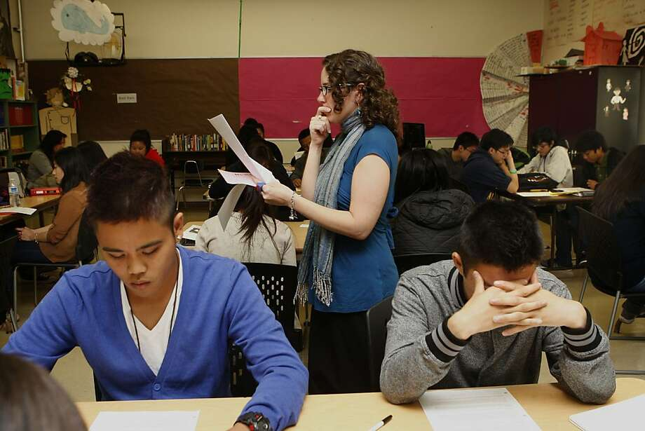 Brian Flores (left), 16 years old, and Sam Ng (right), 17 years old, study  as teacher Savin Teresa (middle) passes by at Burton High School in San Francisco, Calif.  Students start their  first day of school during honors English class on Monday, August  20, 2012. Photo: Liz Hafalia, The Chronicle