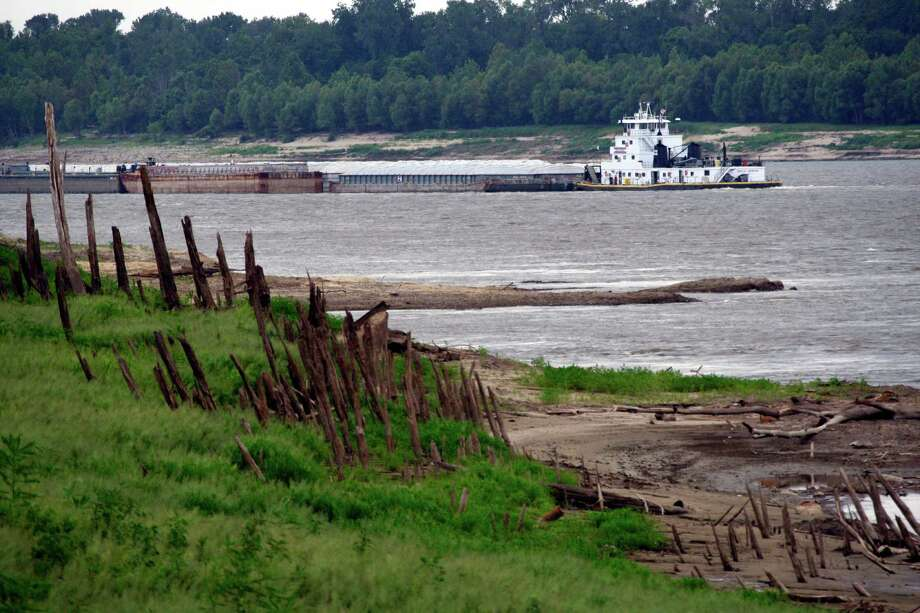 A barge passes exposed sandbars, riverbed and driftwood in shallow waters of the Mississippi at Vicksburg, Miss., in late July. From Illinois to Louisiana, water levels in the river have fallen due to the Midwest drought. Photo: Rogelio V. Solis / AP