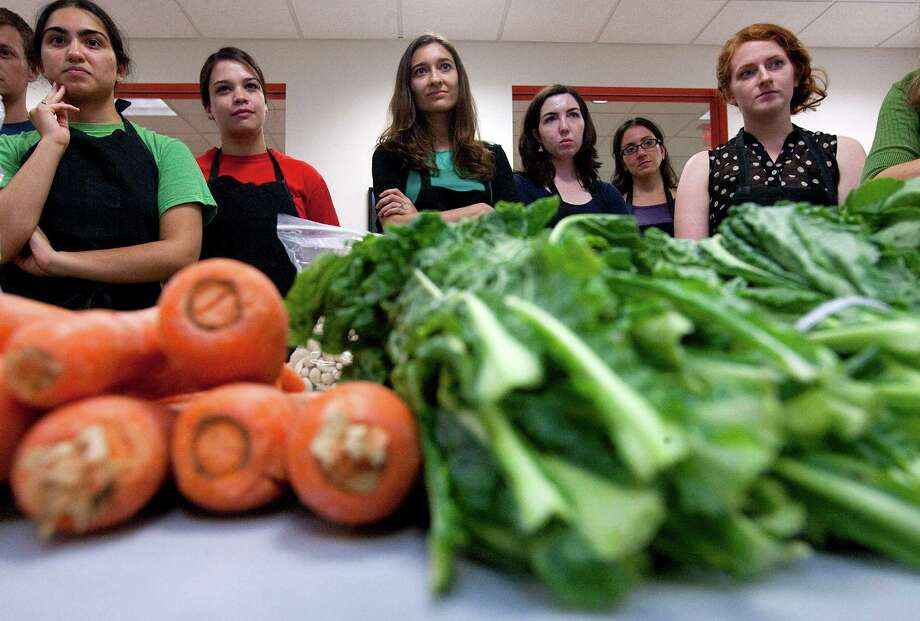 A group of second year medical students watch Roots Bistro chef German Mosquera lead a cooking class at the Baylor College of Medicine in the Texas Medical Center Thursday, Aug. 9, 2012, in Houston.  The students are lectured on the importance of eating well and then join Mosquera for hands-on experience in cooking healthy meals.  The idea is that this will inspire the future physicians to both eat a decent diet themselves and encourage their patients to do so. Photo: Johnny Hanson, Houston Chronicle / © 2012  Houston Chronicle