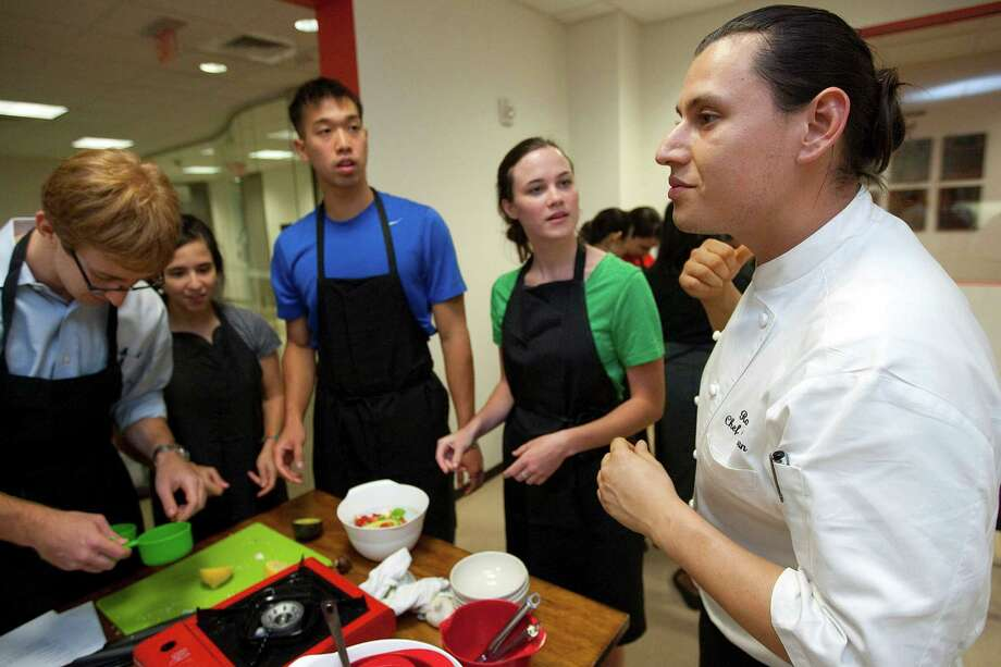 Roots Bistro chef German Mosquera, right, leads a group of second year medical students as they make an avocado and pepper soup in a cooking class at the Baylor College of Medicine in the Texas Medical Center Thursday, Aug. 9, 2012, in Houston. 
