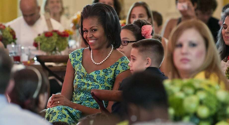 "US First Lady Michelle Obama sits with guests as they eat lunch during a Kids' ""State Dinner"" in the East Room of the White House in Washington, DC, August 20, 2012. This first time event includes 54 kids, ages 8-12, from all US states, three territories and Washington, DC, to a luncheon in support of the Let's Move campaign, featuring healthy recipes and a performance by Nickelodeon's Big Time Rush. AFP PHOTO / Saul LOEBSAUL LOEB/AFP/GettyImages Photo: Saul Loeb, AFP/Getty Images"
