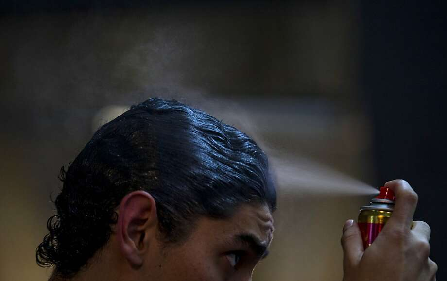 Participant Ramiro Perez sprays his hair before competing during the 2012 Tango Dance World Cup in Buenos Aires, Argentina, Monday, Aug. 20, 2012. The two-week long event offers more than 500 free dance lessons, concerts and recitals. Hundreds of professional dancers compete in the championship and teach many the eight basic steps of the dance in the city where it was born. (AP Photo/Natacha Pisarenko) Photo: Natacha Pisarenko, Associated Press