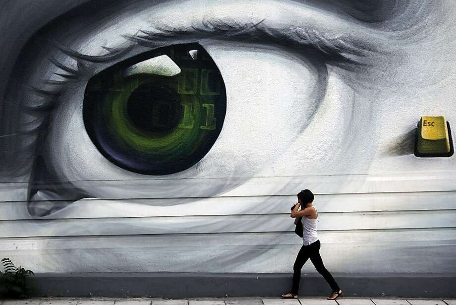 A pedestrian, above, walks past a giant graffiti artwork of an eye painted on a wall in Athens. Photo: Angelos Tzortzinis, Bloomberg