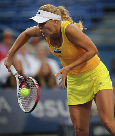 Four time defending champion Caroline Wozniacki hits a backhand volley in her opening round match against Ekaterina Makarova at the New Haven Open at Yale on Monday, August 20, 2012. Photo: Brian A. Pounds, Brian A. Pounds/Connecticut Post / Connecticut Post