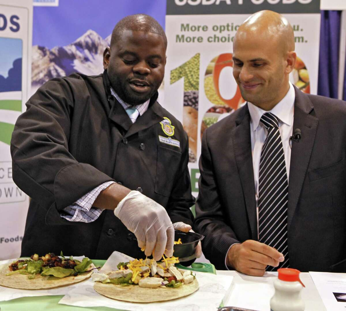 In this July 17, 2012 photo Kern Halls, , a former Disney World restaurant manager who now works in school nutrition Orange County (Fla.) Public Schools, left, demonstrates the making of a wrap for school lunches during the School Nutrition Association conference in Denver asWhite House chef Sam Kass watches. There are plenty of vegetables and other healthy options on school menus these days. The challenge is getting children to eat them. (AP Photo/Ed Andrieski)