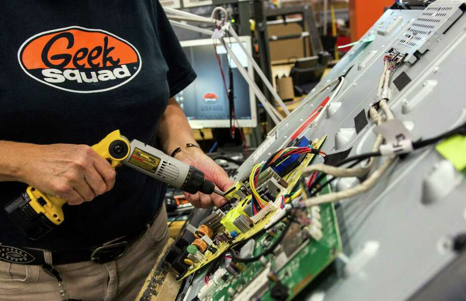 A Geek Squad employee removes flat screen television parts in the TV reclamation area at Geek Squad City in Hillview, Ky., last month. Best Buy offers the Geek Squad service to fix computers and solve other problems. Photo: Ken James / © 2012 Bloomberg Finance LP