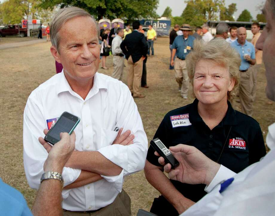 "In this Thursday, Aug. 16, 2012 photograph, Rep. Todd Akin, R-Mo., and his wife Lulli, talk with reporters while attending the Governor's Ham Breakfast at the Missouri State Fair in Sedalia, Mo. Akin was keeping a low profile, Monday, Aug. 20, 2012, a day after a TV interview in which he said that women's bodies can prevent pregnancies in ""a legitimate rape"" and that conception is rare in such cases. (AP Photo/Orlin Wagner) Photo: Orlin Wagner"