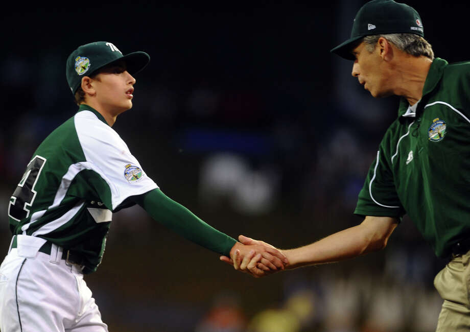 New England pitcher Will Lucas shakes head coach Bill Meury's hand after completing an inning, during 2012 Little League World Series game action in South Williamsport, Penn. on Monday August 20, 2012. Photo: Christian Abraham / Connecticut Post