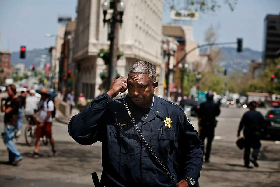 Oakland police Lt. Freddie Hamilton talks on his radio in May. AT&T has partially disabled 16 cell phone towers after they were found to cause radio failures among police and firefighters. Photo: Jason Henry, Special To The Chronicle