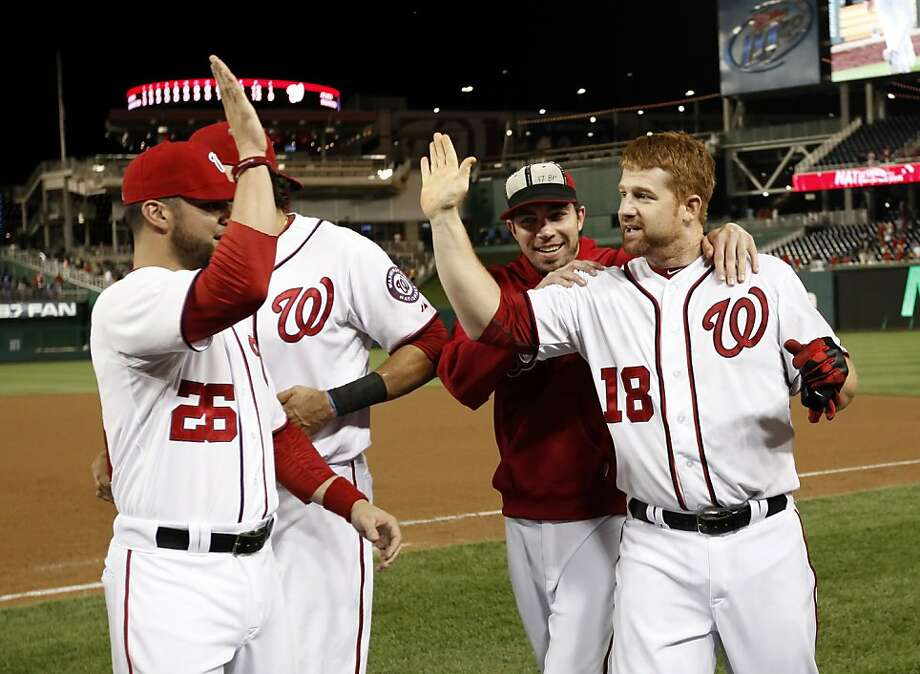 Chad Tracy, far right, singled in the 13th inning Monday night to score Danny Espinosa with the winning run in a matchup of the NL East's top teams. Photo: Alex Brandon, Associated Press