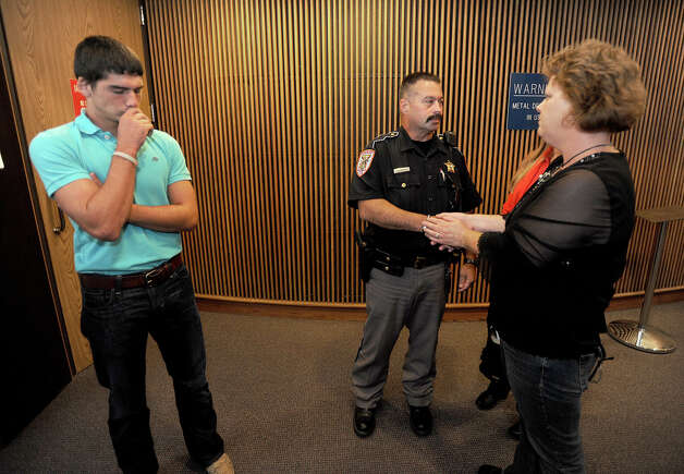 Two family members, right, of Dillon Dwight Schlegel, 17, hug and shake hands with Orange County Deputy Fred Ashworth in an apologetic gesture after the 30-year-sentencing of Schlegel at the Jefferson County Courthouse on Monday. The sentencing stemmed from a January incident where Schlegel shot Fred Ashworth in the chest at the Jefferson County Jail. Jacob Ashworth is also pictured. Photo taken Monday, August 20, 2012. Guiseppe Barranco/The Enterprise Photo: Guiseppe Barranco, STAFF PHOTOGRAPHER / The Beaumont Enterprise
