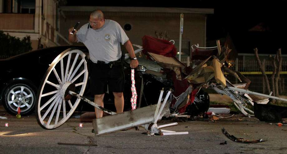 Officer Jeremy Smart investigates the scene of an accident that left one person dead and four injured after a car slammed into a horse-drawn carriage in the 1200 block of 21st Street in Galveston late Saturday. JENNIFER REYNOLDS/The Daily News Photo: Jennifer Reynolds, Photo Editor / The Galveston County Daily News 2012