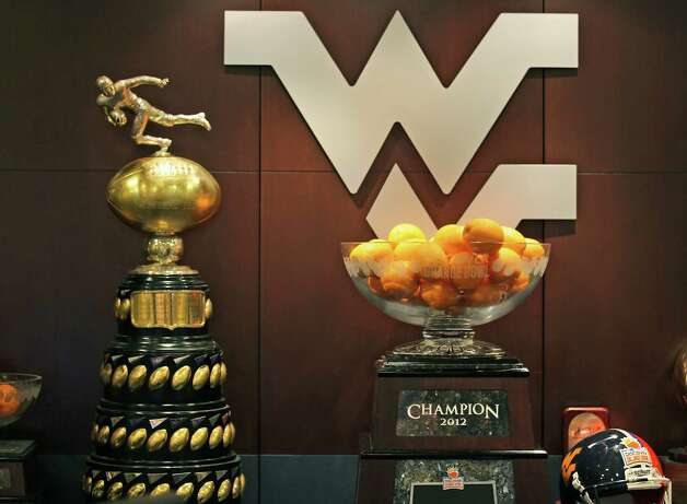 West Virginia University Mountaineers's won the Eastern College Football Championship in the 2011 season with the Lambert Trophy left, and winners of the 2012 Orange Bowl, right.  The school is the newest team to join the Big 12 Conference.  Thursday, Aug. 9, 2012. Photo: Bob Owen, San Antonio Express-News / © 2012 San Antonio Express-News