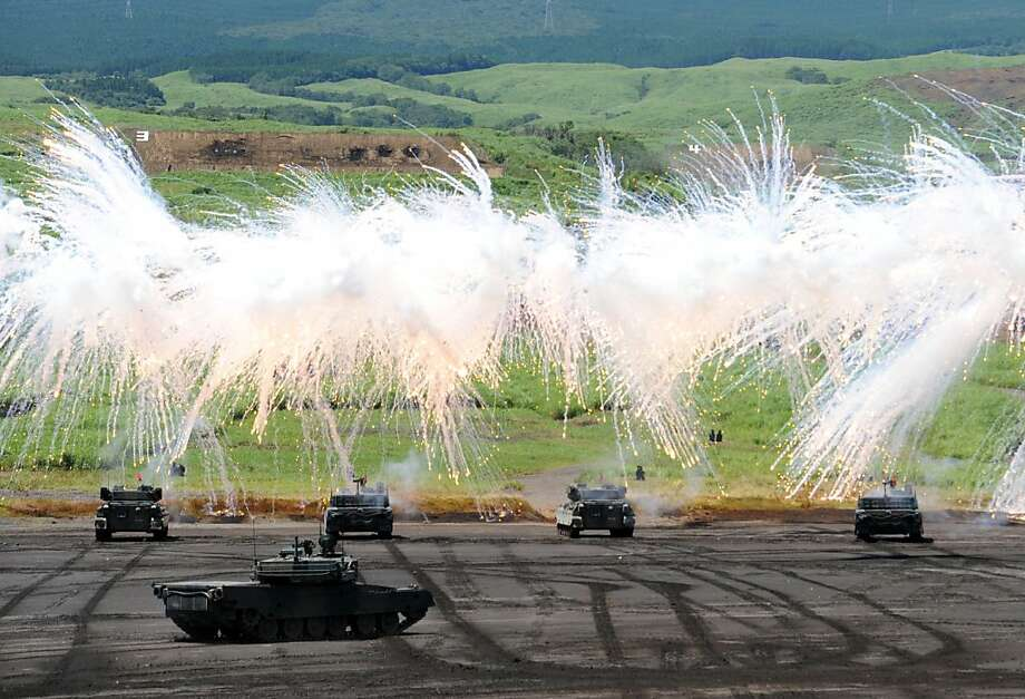 Japanese Ground Self-Defense Forces tanks move amongst an umbrella of barrage during an annual live fire exercise at the Higashi-Fuji firing range in Gotemba, at the foot of Mt. Fuji in Shizuoka prefecture on August 21, 2012. The annual drill involves some 2,400 personnel, 80 tanks and armoured vehicles and 30 aircraft and helicopters.  Photo: Yoshikazu Tsuno, AFP/Getty Images
