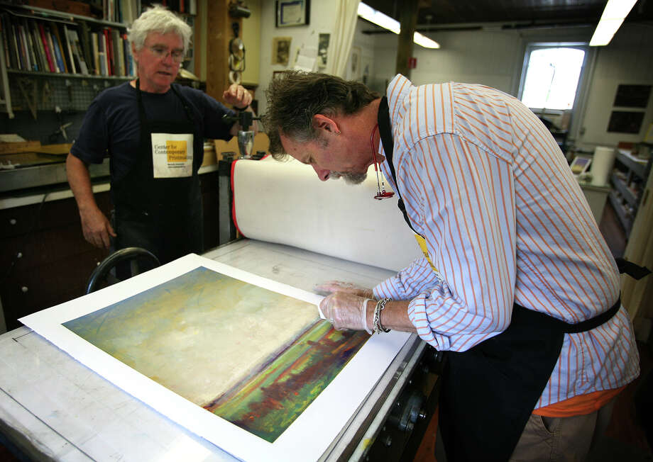 With the assistance of master printmaker Tony Kirk, left, artist Will McCarthy of Hamden works on a monotype print in a series of atmospheric landscapes at the Center for Contemporary Printmaking in Norwalk. McCarthy will showcase his work in a gallery exhibit at the center opening September 16. Photo: Brian A. Pounds / Connecticut Post