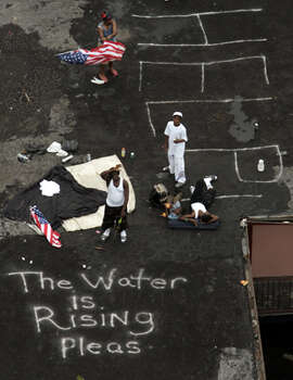 Residents wait on the roof of an apartment complex to be evacuated from the floodwaters of New Orleans after Hurricane Katrina, Thursday, Sept. 1, 2005. Photo: .