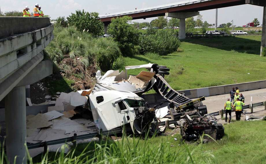 An 18-wheeler ran off the Gulf Freeway as the driver was attempting to curve on ramp merging onto 610 eastbound loop when it struck the guardrail and drove on to the Broadway exit below ramp on Tuesday, Aug. 21, 2012, in Houston.  Driver was wearing his seatbelt, and only suffered a scratch on his elbow. Photo: Mayra Beltran, Houston Chronicle / © 2012 Houston Chronicle