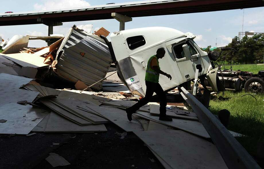 Clean up crew walks around debris from the 18-wheeler accident along 610 Southeast loop and Gulf Freeway on Tuesday, Aug. 21, 2012, in Houston. The 18-wheeler ran off the Gulf Freeway as the driver was attempting to curve on ramp merging onto 610 eastbound loop when it struck the guardrail and drove on to the Broadway exit below ramp. Driver was wearing his seatbelt, and only suffered a scratch on his elbow. Photo: Mayra Beltran, Houston Chronicle / © 2012 Houston Chronicle
