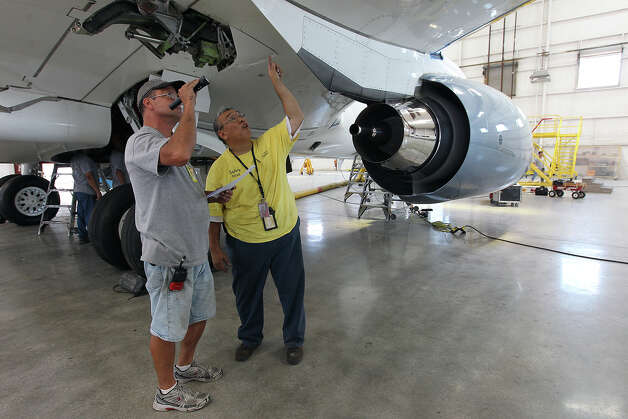 AERIA Luxury Interiors employees inspect under the wing of a private Boeing 757 on Wednesday, August 8, 2012. AERIA is a subsidiary of ST Aerospace San Antonio. AERIA is a new niche operation for ST Aerospace that customizes aircraft to the needs of the private aircraft owners. ST Aerospace has traditionally been a maintenance facility for commercial aircraft and has been in San Antonio since 2002 when the company acquired operations from Dee Howard Aircraft Maintenance. Photo: Kin Man Hui, SAN ANTONIO EXPRESS-NEWS / ©2012 San Antonio Express-News