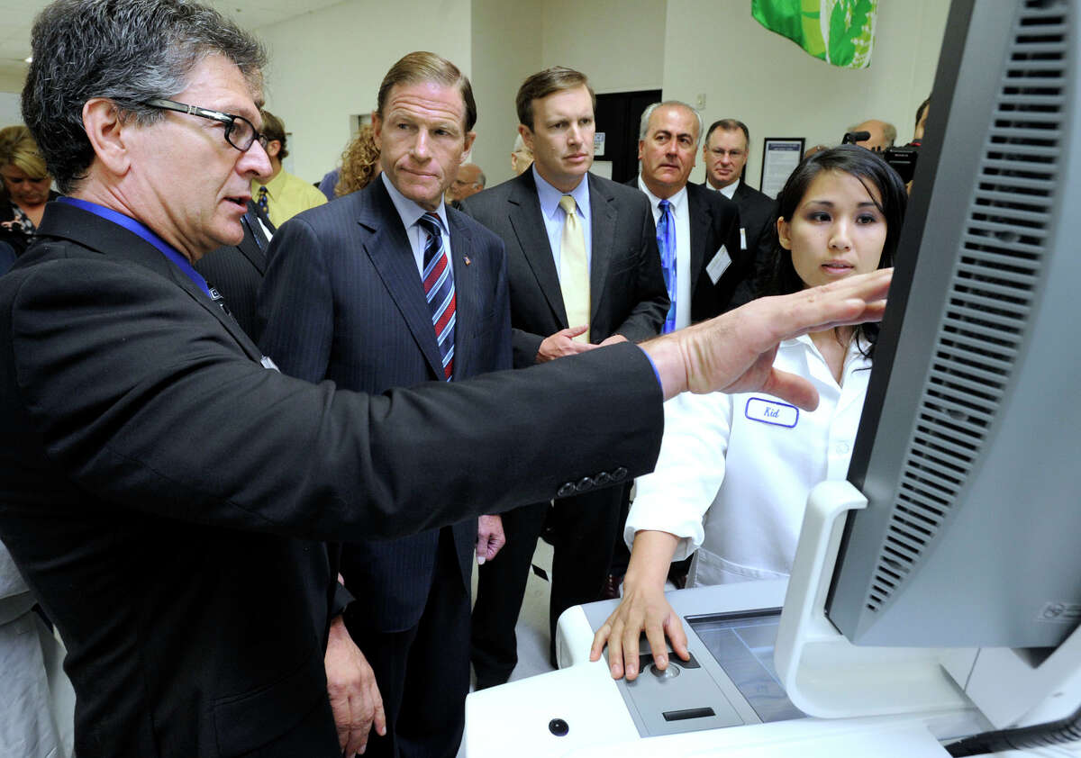Phil Accardo, left, test engineering manager at Hologic Inc. in Danbury, talks about a 3D mammography machine to U.S. Sen. Richard Blumenthal, left center, and U.S. Rep. Chris Murphy during a tour, Tuesday, Aug. 21, 2012. Right is Chindavone Meksavanh, an electronic technician.