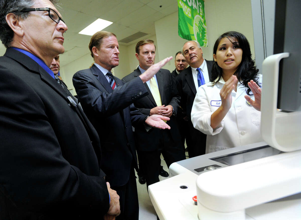 Phil Accardo, left, test engineering manager at Hologic Inc., listens as Chindavone Meksavanh, an electronic technician, right, talks about a 3D mammography machine to U.S. Senator Richard Blumenthal, left center, and U.S. Rep. Chris Murphy during a tour of the Danbury facility, Tuesday, Aug. 21, 2012.