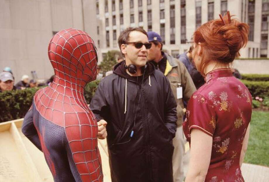 "50-years of Spider-Man- The web-flying superhero made his first debut in the comic book ""Amazing Fantasy."" In this photo Director Sam Raimi and actors Tobey Maguire and Kirsten Dunst talk on the set of the movie ""Spider-Man,"" on April 19, 2001. (Getty Images)"
