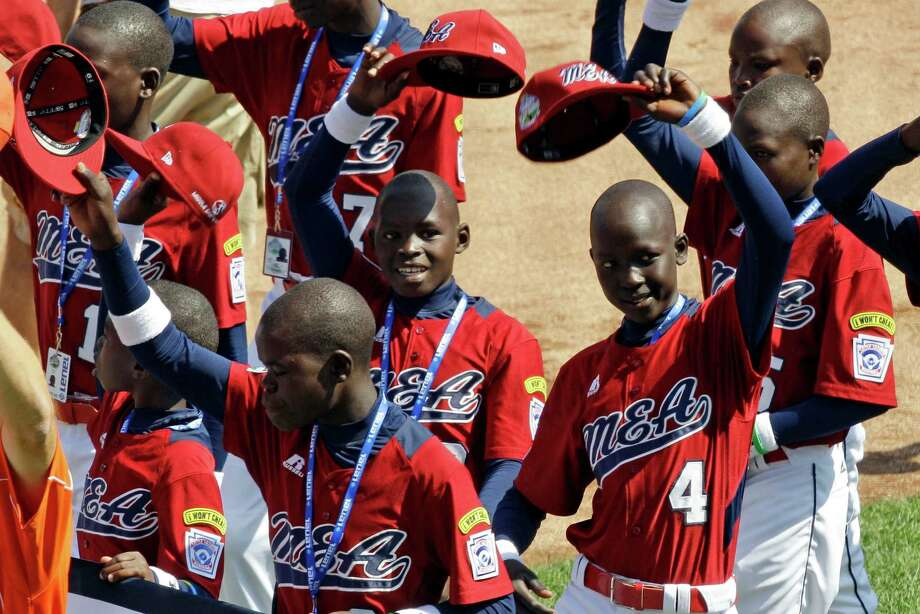 The  team from Lugazi, Uganda, acknowledging the crowd during opening ceremonies, was the first African team ever to appear in the  Little League World Series. Photo: Gene J. Puskar, Associated Press / AP