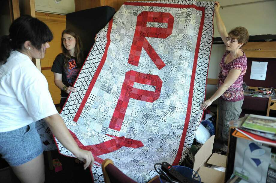 Freshman Priscilla Acosta, left, from Miami, and her roommate, Adrianne Kunkel, from Canton, Conn., unroll a quilt made by Adrianne's mom, Jackie Kunkel, right, as they set up their dorm room during freshman move-in day at RPI on Tuesday, Aug. 21, 2012 in Troy, NY. Jackie Kunkel said she started making the quilt in June and that each of the smaller pieces of the quilt have graphic icons of things her daughter loves.  (Paul Buckowski / Times Union) Photo: Paul Buckowski