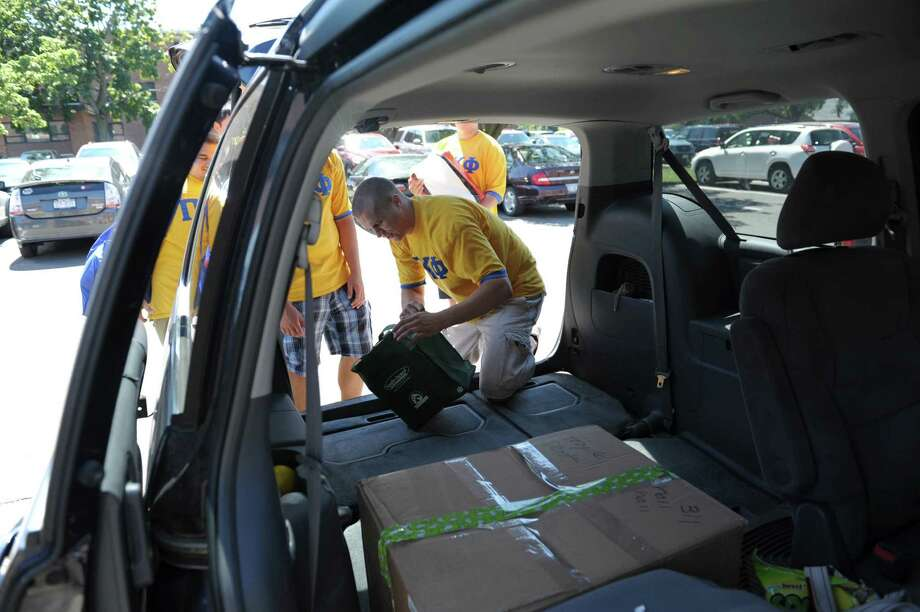 A.J. Nihill, a member of the Pi Kappa Phi fraternity, passes items to his fellow fraternity members as they unloaded items of a new student during freshman move-in day at RPI on Tuesday, Aug. 21, 2012 in Troy, NY.    (Paul Buckowski / Times Union) Photo: Paul Buckowski