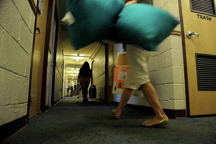 Students and family members carry in their belonging to a dorm room during freshman move-in day at R