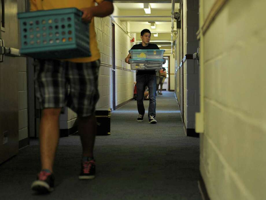 Timothy Lim, a member of the Pi Delta Psi fraternity, helps carry the items of an incoming freshman during freshman move-in day at RPI on Tuesday, Aug. 21, 2012 in Troy, NY.  Members of fraternities and sororities helped to unload the cars for the new students and their families.  (Paul Buckowski / Times Union) Photo: Paul Buckowski