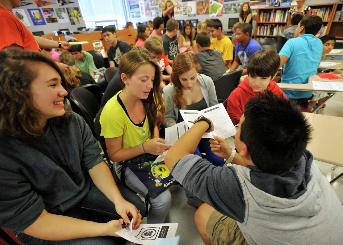 From left, Amanda Deming, Keely Sproviero, Laura Kavallines, Elliot Pollard and Simon Garcia work in a group to learn about the different capstone project choices during freshman orientation at Bethel High School on Tuesday, Aug. 21, 2012.