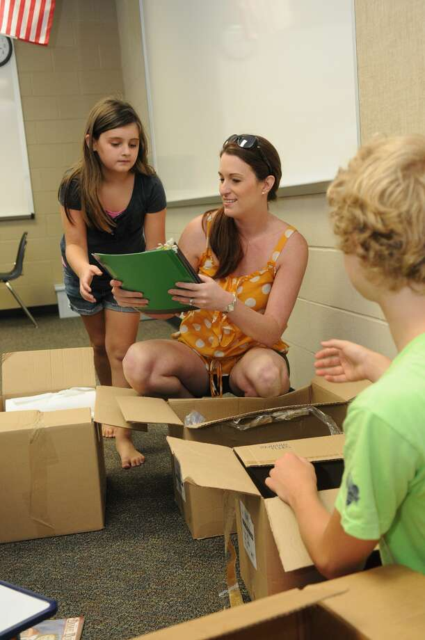 Kelli Power, center, a seventh-grade Texas History teacher at Gerald D. Irons Sr. Junior High School, unpacks supplies in her classroom with help from her children, Emma, left, and Nic. Photo: Jerry Baker